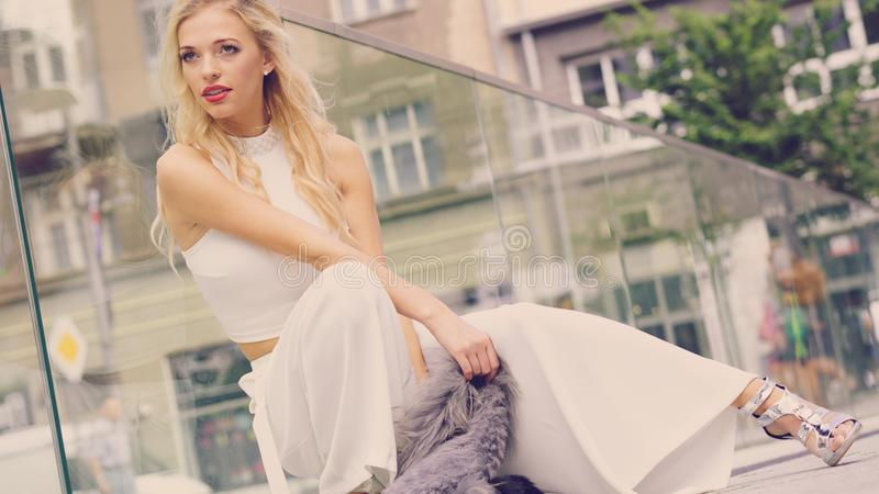 Woman wearing crop top and culottes. Elegant fashionable woman presenting trendy urban outfit. White crop top and trousers culottes. Outdoor photo session stock photo