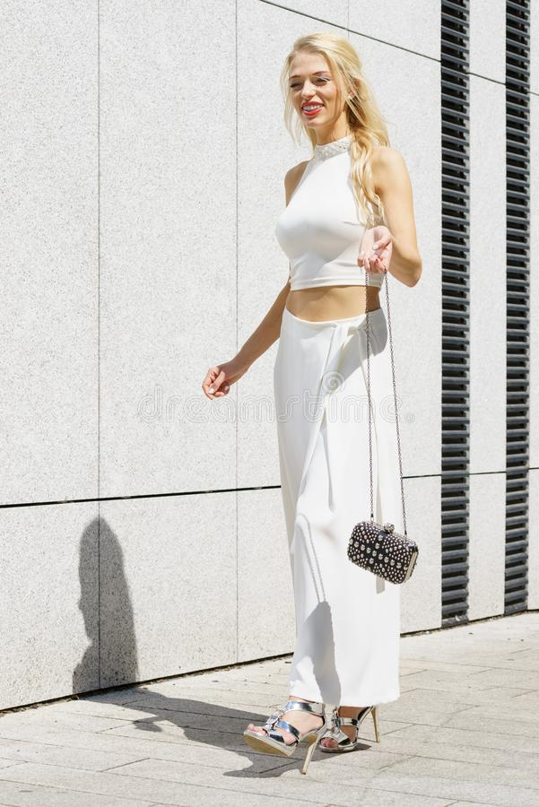 Woman wearing crop top and culottes. Elegant fashionable woman presenting trendy urban outfit. White crop top and trousers culottes stock photo