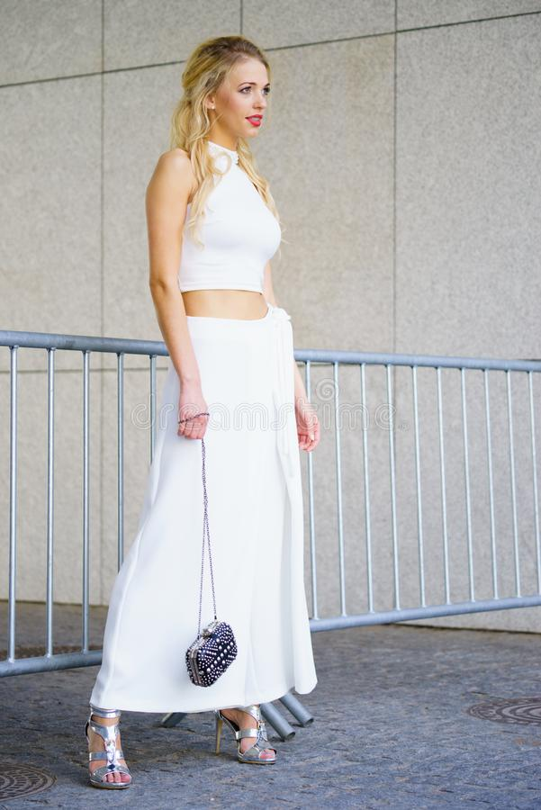 Woman wearing crop top and culottes. Elegant fashionable woman presenting trendy urban outfit. White crop top and trousers culottes stock image