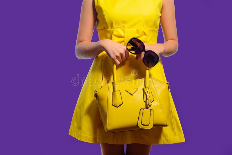 Elegant fashionable woman in yellow dress with handbag and sunglasses stock photography