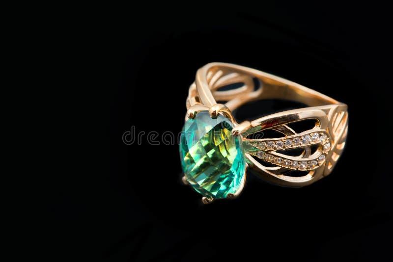 Elegant female jewelry with emerald. Elegant female jewelry ring with jewel stone - emerald, on black background royalty free stock photography