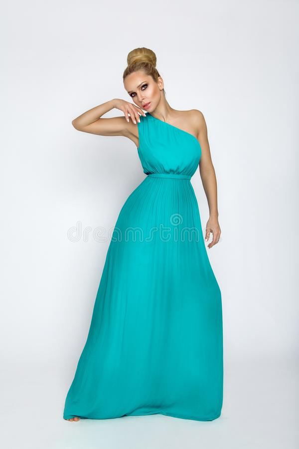 Elegant female model in a turquoise long silk dress standing on a white background. And sensually poses royalty free stock image
