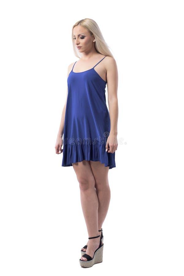 Elegant feminine tender blonde girl wearing dress looking down with arms down and crossed legs royalty free stock images