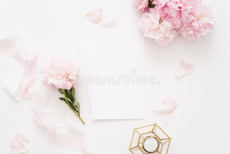 Elegant feminine wedding or birthday flat lay composition with pink peonies. Floral bouquet, silk ribbon and candle Blank paper card, mockup, invitations royalty free stock images