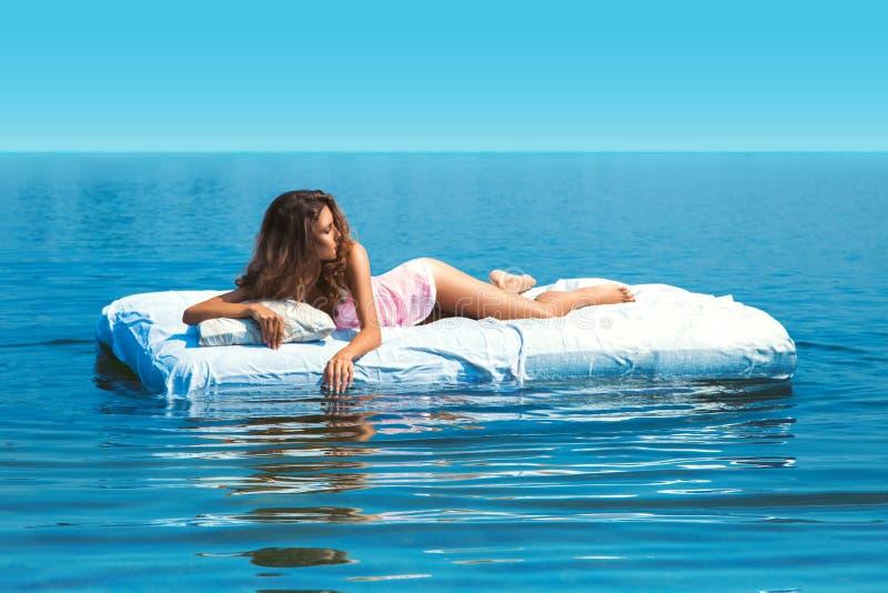 Elegant flicka som ligger på säng i det öppna havet royaltyfri fotografi