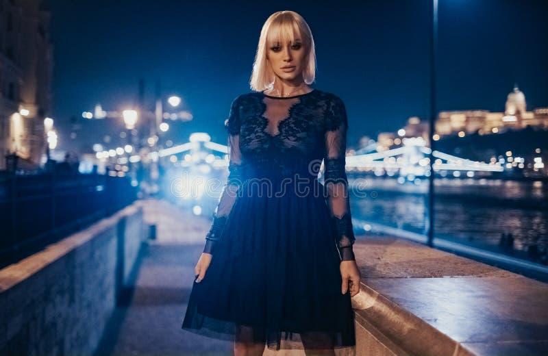 Elegant flickaanseendeyttersida med stadsljus bak henne arkivbild