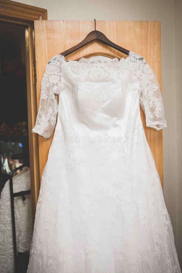Elegant flowing wedding dress hanging from door stock photo