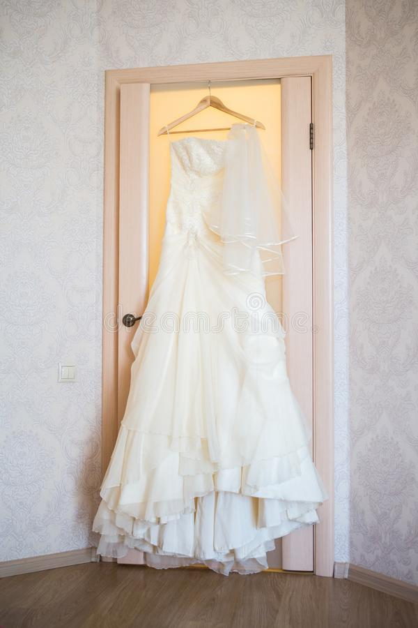Elegant flowing wedding dress hanging from door. Elegant flowing wedding dress hanging on door royalty free stock images