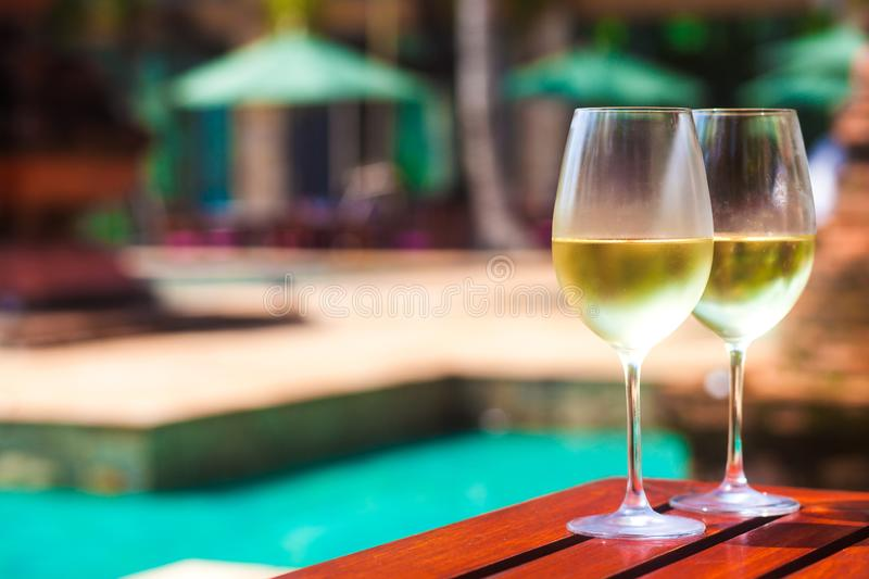 Elegant flute glass of sparkling white wine or champagne by side of swimming pool stock images