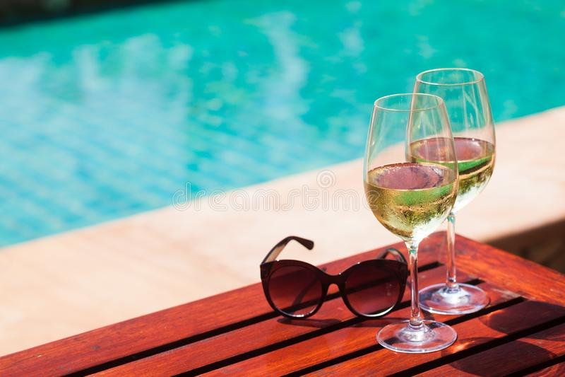 Elegant flute glass of sparkling white wine or champagne by side of swimming pool royalty free stock photo