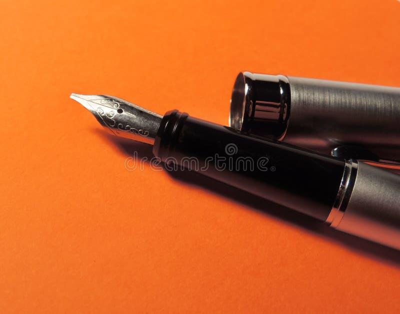 Elegant fountain pen. On orange paper royalty free stock images