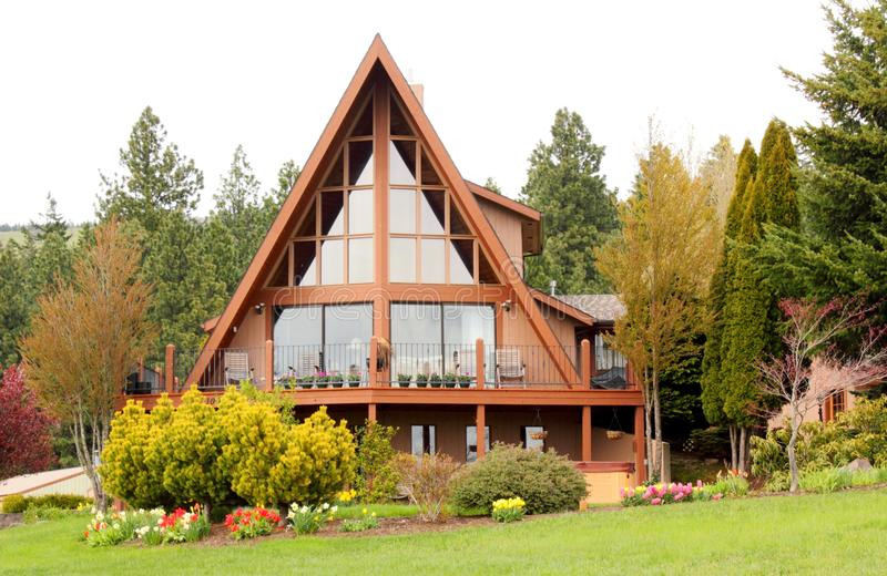 Elegant A Frame Home. An elegant A-Frame house, home with lots of windows, landscaping, and trees in Oregon stock photos