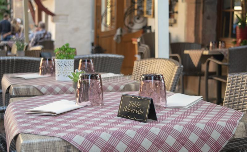 Elegant french Restaurant table with reserved french card. Leisure concept Service industry royalty free stock images