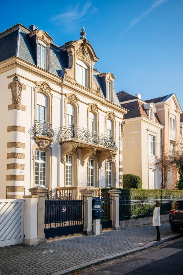 Elegant French woman admiring the luxury house stock photography