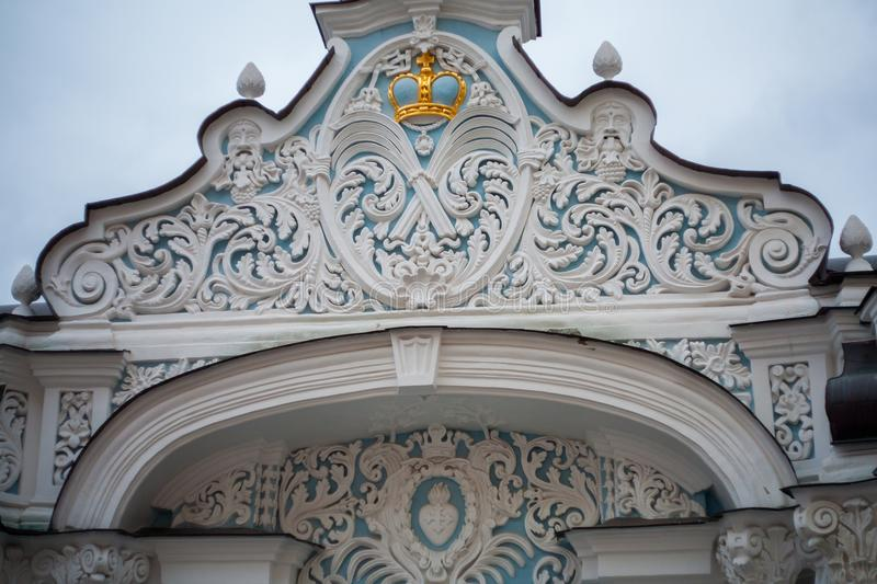 Elegant fretwork in the form of a floral ornament and a golden c. Rown on the monastery gate stock photography