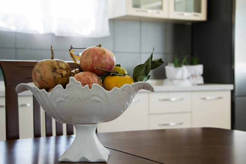 Elegant fruit bowl on the wooden table and modern kitchen interior royalty free stock photos