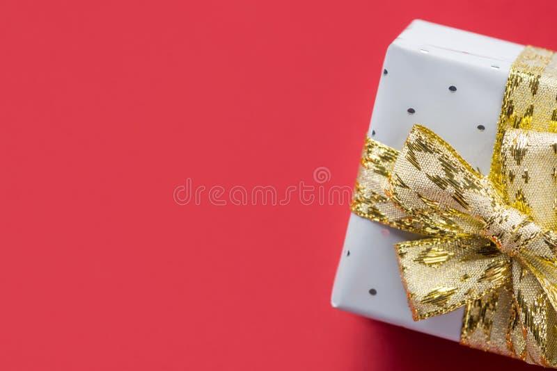 Elegant gåvaask som slås in i silverpapper som binds med guld- den mörka bandpilbågen - röd burgundy bakgrund nytt år för jul royaltyfri foto