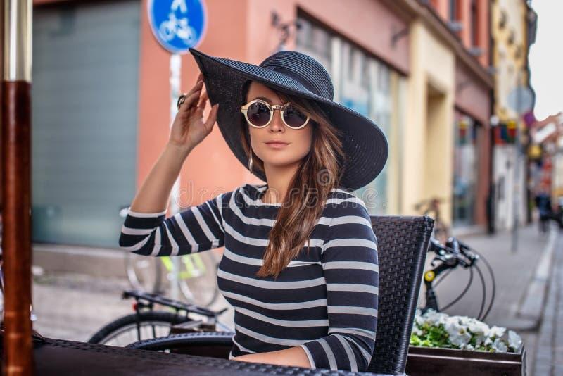 Elegant geklede jonge vrouw die een modieuze hoed en zonnebril dragen die in een koffie van de de zomerstraat zitten royalty-vrije stock fotografie