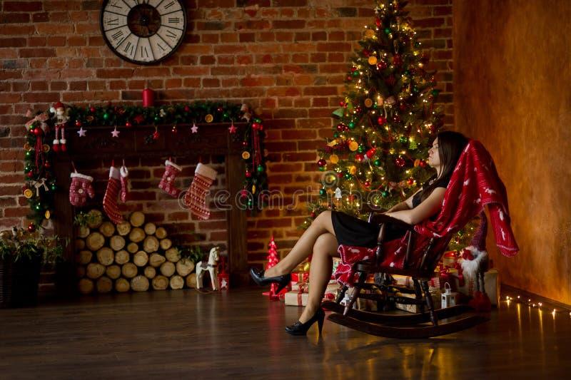 Elegant gekleidete junge Frau sitzt im Schaukelstuhl nahe Weihnachten-Baum lizenzfreies stockfoto
