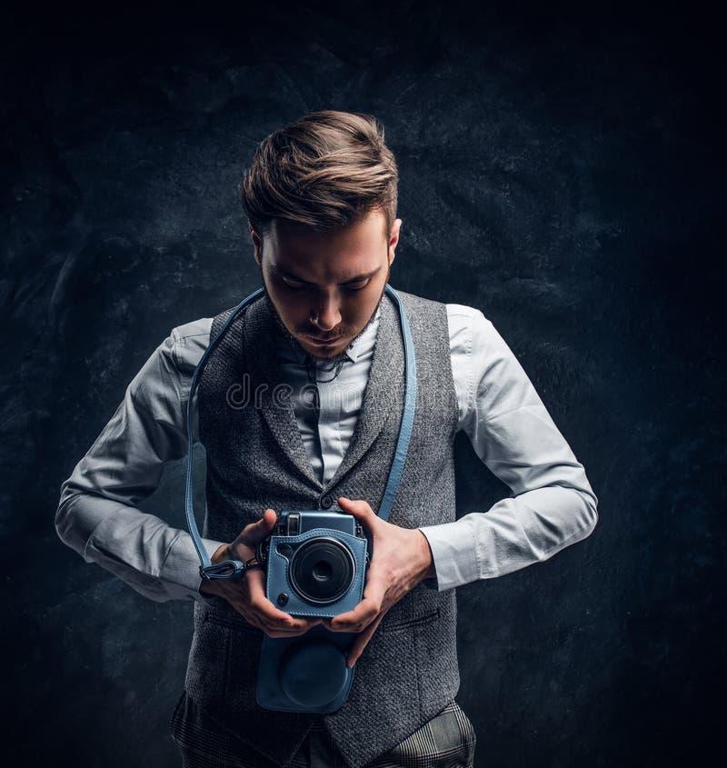 Elegant gekleideter junger Mann, der mit einer Kamera in einem Studio aufwirft stockfoto