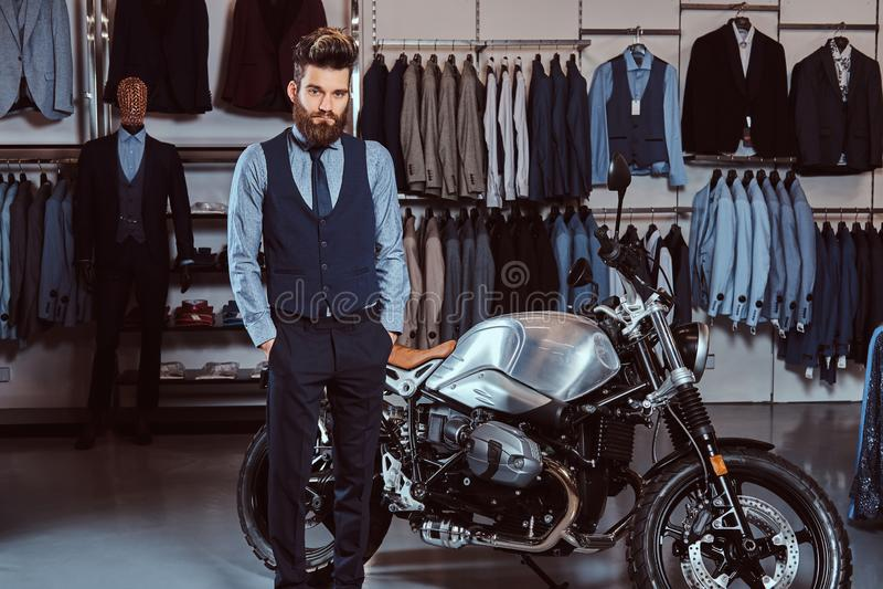 Elegant gekleideter Mann, der mit den Händen in den Taschen nahe Retro- Sportmotorrad am Bekleidungsgeschäft der Männer aufwirft stockbild