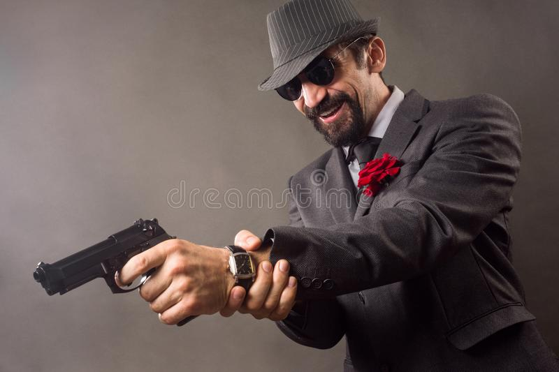 Elegant gentleman with pistol. The smiling elegant gentleman in suit in classical retro style is aiming with pistol or handgun on gray background stock image
