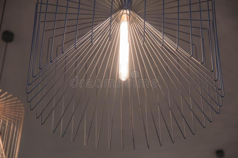 Elegant geometric chandelier made from straight thin metal wire closeup. Minimal lampshade. Lamp with long glass light bulb. Lined shaped background. Urban royalty free illustration