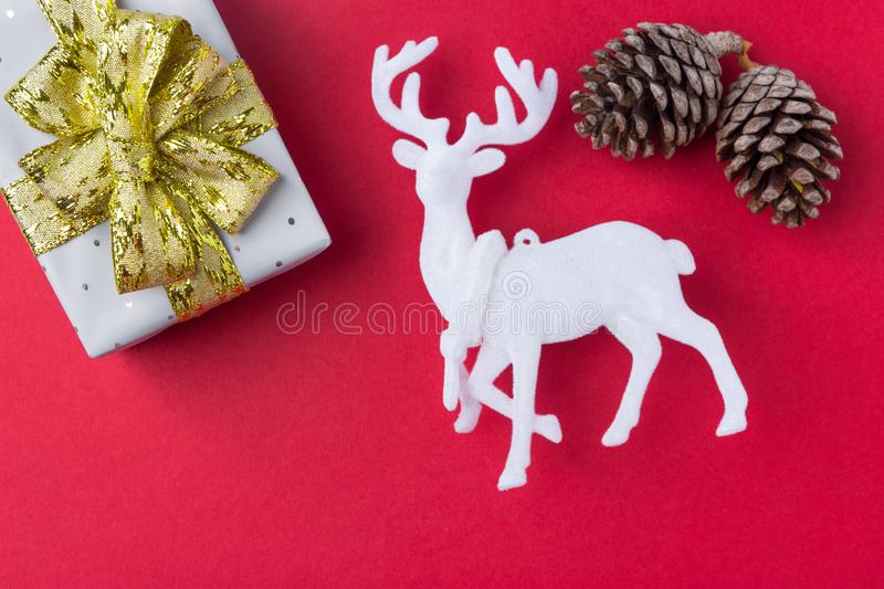Elegant gift box wrapped in silver paper tied with golden ribbon bow white deer pine cones on dark red background. New Year stock image