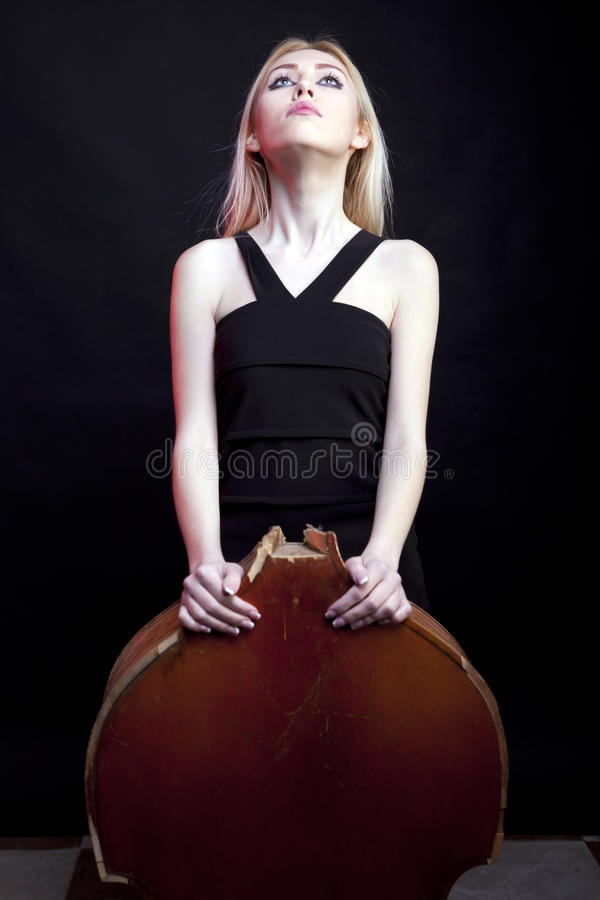 Download Elegant Girl Behind A Broken Contrabass On Black Background Stock Photo - Image: 30446384