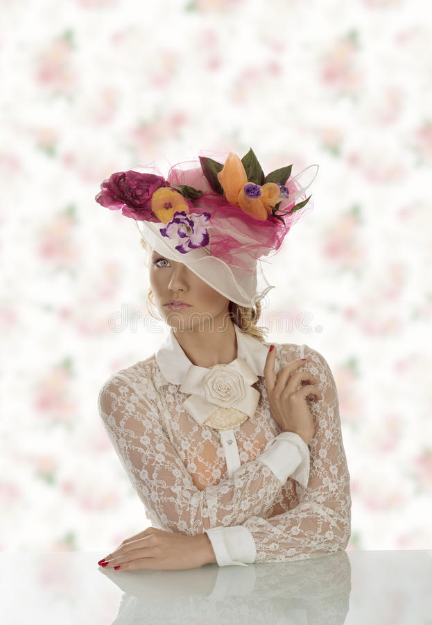 Elegant girl behind table with floral hat covers one eye royalty free stock images