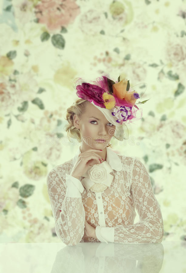 Elegant girl behind table with floral hat and hand under the chi stock images
