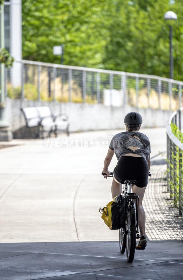Elegant girl on a bicycle supports her slim figure and rides on the sidewalk stock photo
