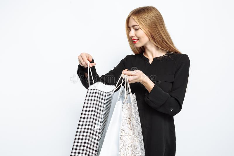Elegant girl in black dress and with red lips, with bags, for sh. Opping, happy after a successful shopping, Black Friday, discounts royalty free stock image