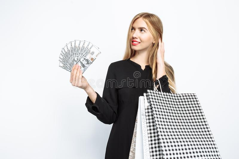 Elegant girl in black dress and with red lips holds packages and. Elegant girl in black dress and with red lips holding packages and money getting ready for royalty free stock photography