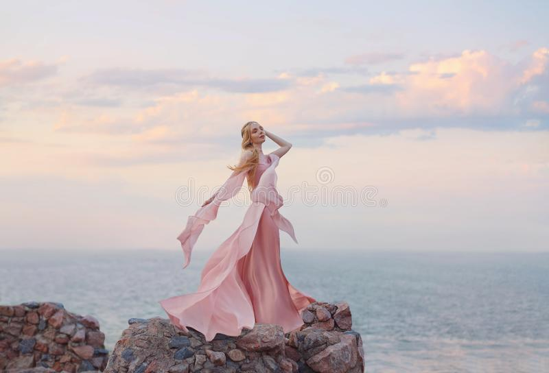 Elegant girl elf with blond fair wavy hair with tiara on it, wearing a long light pink rose rozy fluttering dress. Standing on the high tower of the old castle royalty free stock photos
