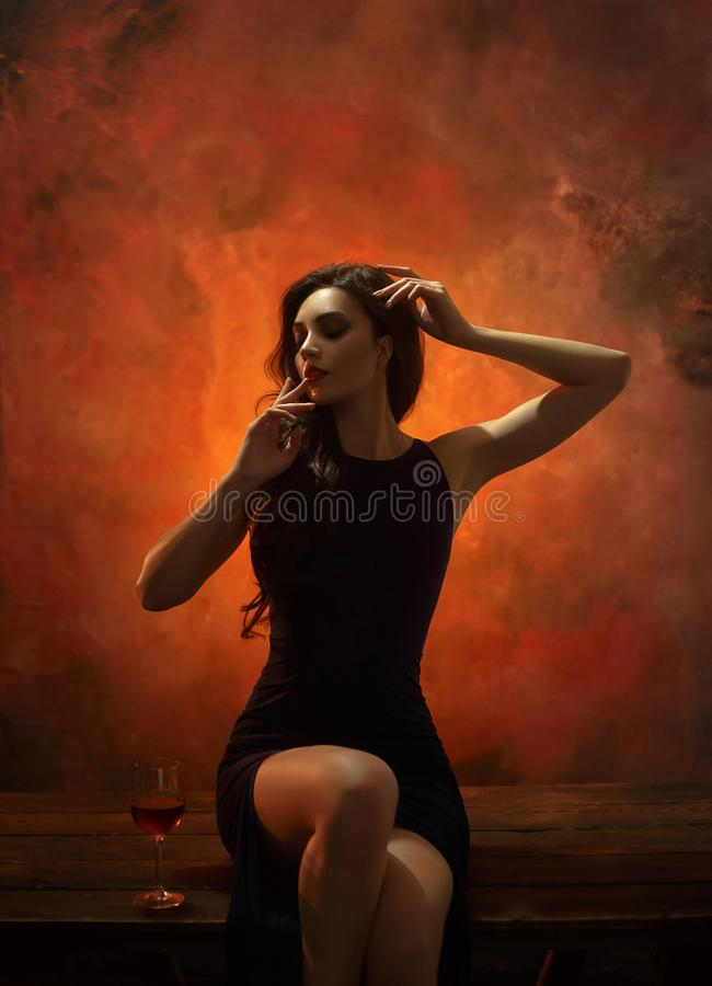 Elegant girl in evening dress. Exquisite styling - Hollywood wave, make-up smoky eyes and red lips. The background is a fiery wall stock image