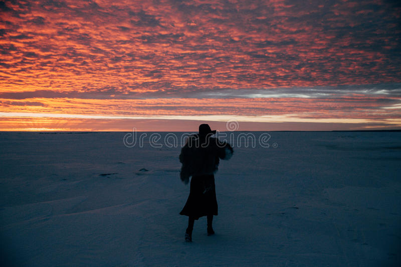Elegant girl in fur coat and hat at sunset royalty free stock photography