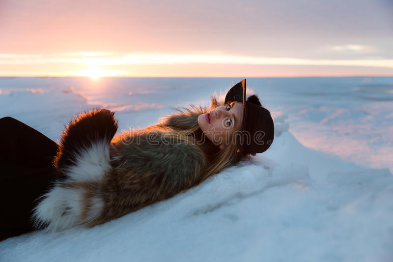 Elegant girl in fur coat and hat at sunset royalty free stock photo