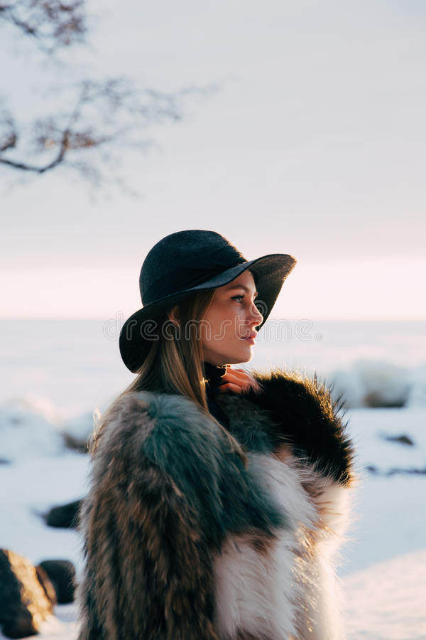 Elegant girl in fur coat and hat at sunset stock photos