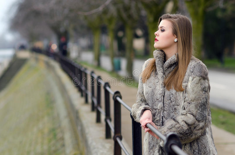 Elegant girl in fur coat walking alone in winter city alley stock images