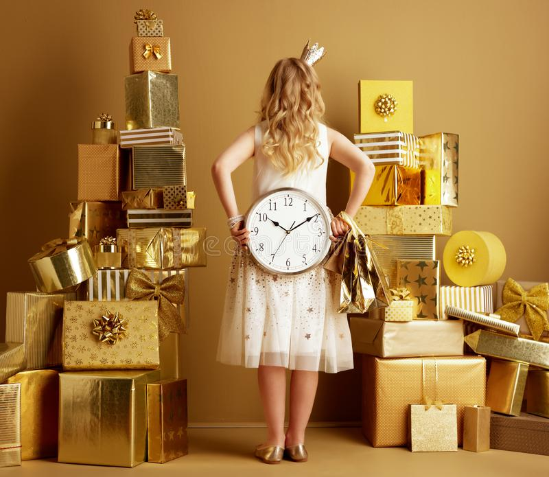Elegant girl with gold shopping bags showing round clocks royalty free stock photography