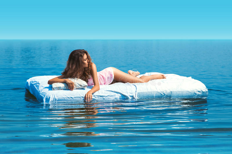 Elegant girl lying on bed in open sea royalty free stock photography