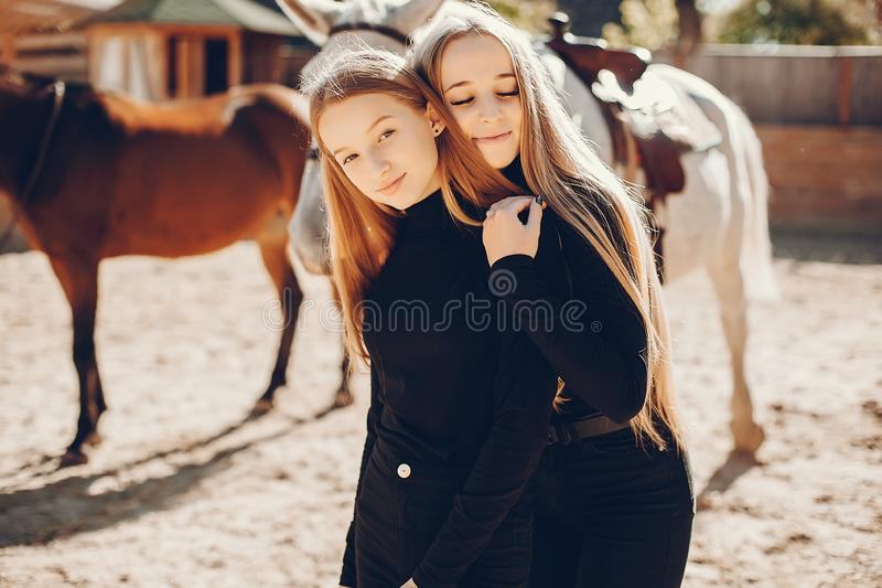 Elegant girls with a horse in a ranch royalty free stock photo