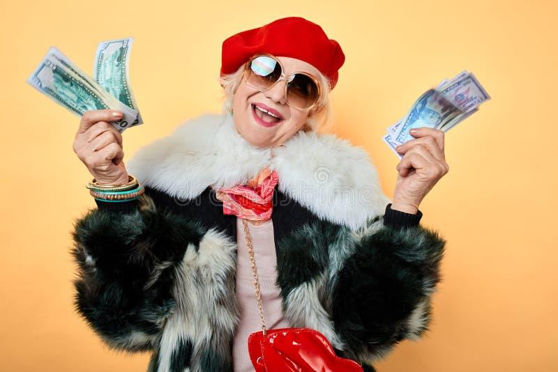 Elegant gladlynt kvinna med lyftta armar som visar hennes pengar arkivfoto