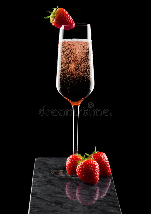 Elegant glas roze roze champagne met aardbei op hoogste en verse bessen op zwarte marmeren raad op zwarte achtergrond royalty-vrije stock afbeeldingen