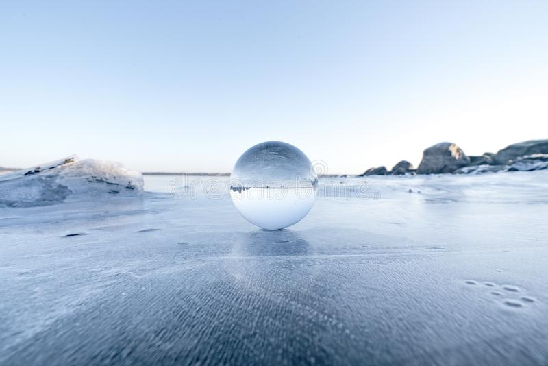 Elegant glass orb on ice on a frozen lake stock photography