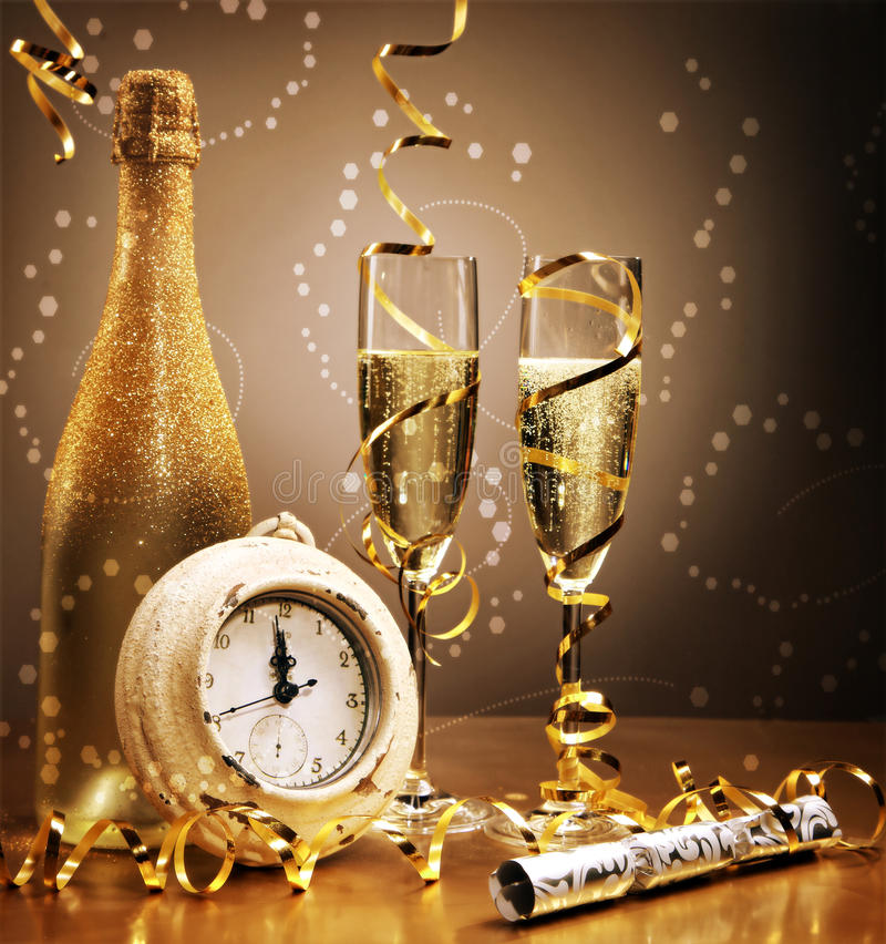 Elegant gold New Year still life. With a clock counting down to midnight in front of a bottle and flutes of sparkling champagne with golden streamers and a royalty free stock image