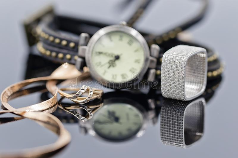 Elegant gold ring and chain lie on the background of women`s wat stock photography