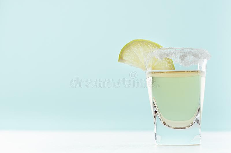 Elegant golden tequila in shot glass with rim of salt and slice lime on pastel mint color background, copy space. royalty free stock image