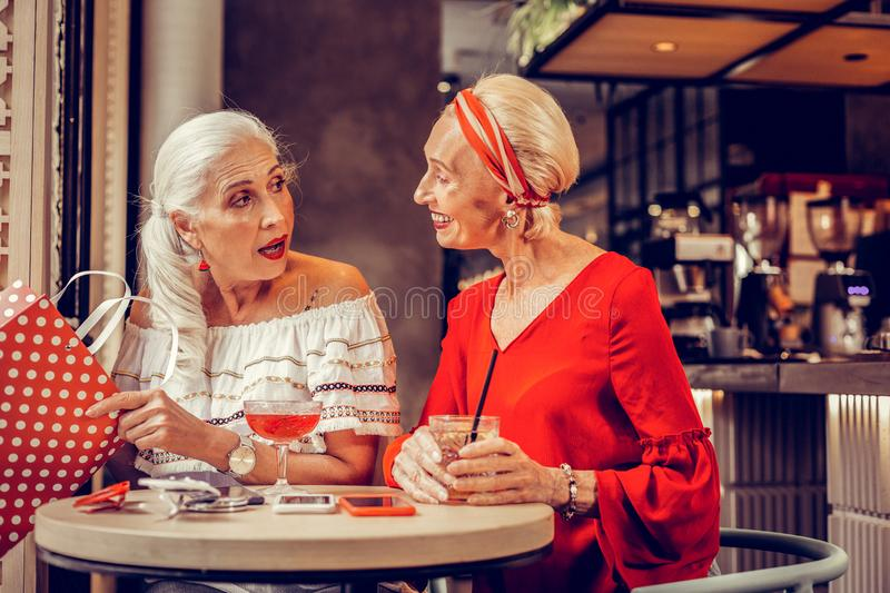 Elegant good-looking short-haired woman talking to her friend stock images